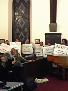 People encircle the sanctuary, holding signs that represent all the towns that have voted against the pipeline