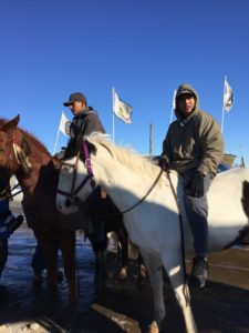Young men on horseback assembling as they prepare to lead the way in rebuilding the Sacred Hoop